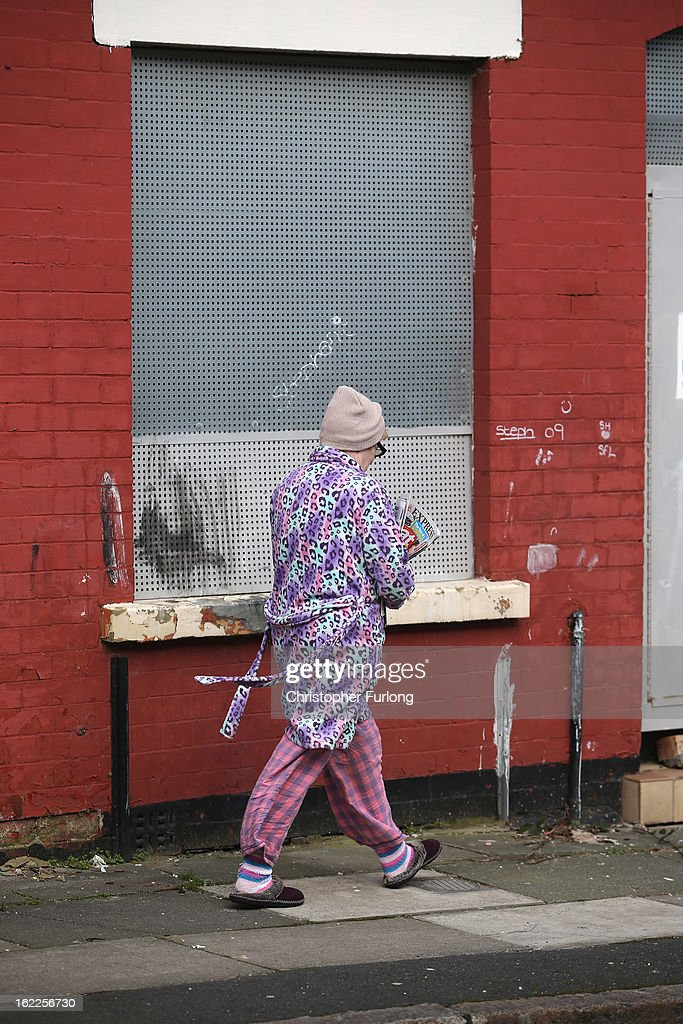 A woman walks past derelict homes in Arnside Road, in the Kensington area of Liverpool, one of the locations in the 'Granby Triangle' on February 21, 2013 in Liverpool, England. Liverpool Council are proposing to sell off a selection of it's derelict housing stock for one GB Pound each in the failed redevelopment area known as the Granby Triangle.