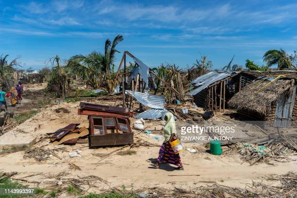 Woman walks past destroyed houses on May 13 on her way to an aid distribution centre in the coastal village of Guludo on Ibo Island, in Mozambique's...