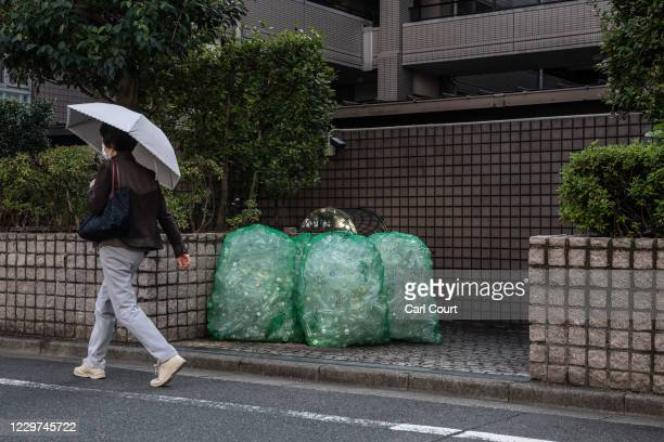 A woman walks past disposed polyethylene terephthalate plastic bottles that have been placed outside an apartment block for collection on November 19...