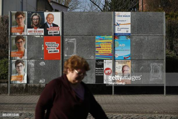 A woman walks past election campaign posters on March 15 2017 in Schwalbach Germany Schwalbach is in the industrial heartland of Saarland the small...