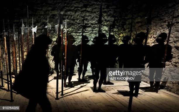 A woman walks past figures of medieval knight silhouettes inside the watchtower of the Chateau De Chillon in Montreux on January 25 2018 / AFP PHOTO...