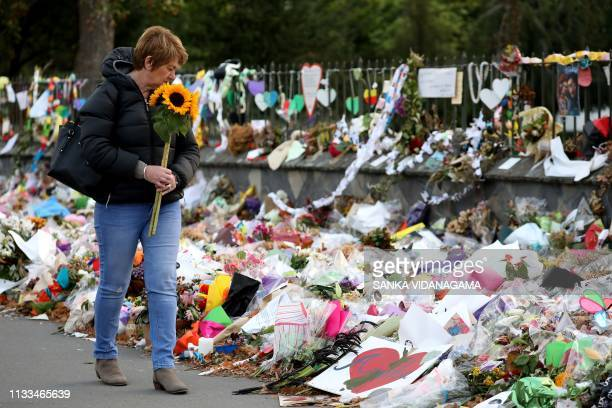 Woman walks past flowers and tributes displayed in memory of the twin mosque massacre victims at the Botanical Garden in Christchurch on March 29,...