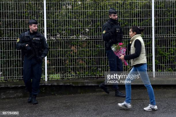 TOPSHOT A woman walks past gendarmes standing guard in front of the Gendarmerie Nationale in Carcassonne on March 24 2018 as she carries flowers in...