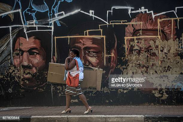 A woman walks past graffiti depicting late South African leader Nelson Mandela on the third anniversary of his passing in Soweto southwest of...