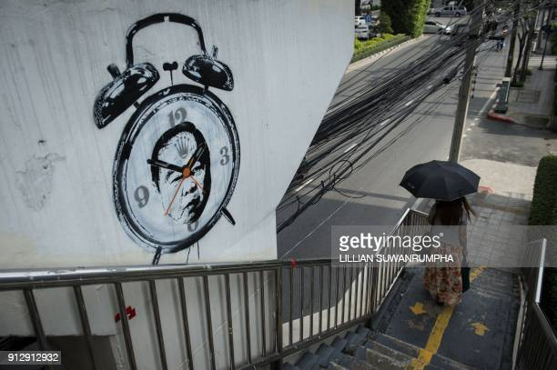 A woman walks past graffiti depicting Thailand's junta number two Prawit Wongsuwan who is currently mired in a corruption scandal over his collection...