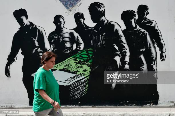 A woman walks past graffiti in the Greek capital Athens by French street artist Goin on July 25 2017 Greece will make its first return to the debt...