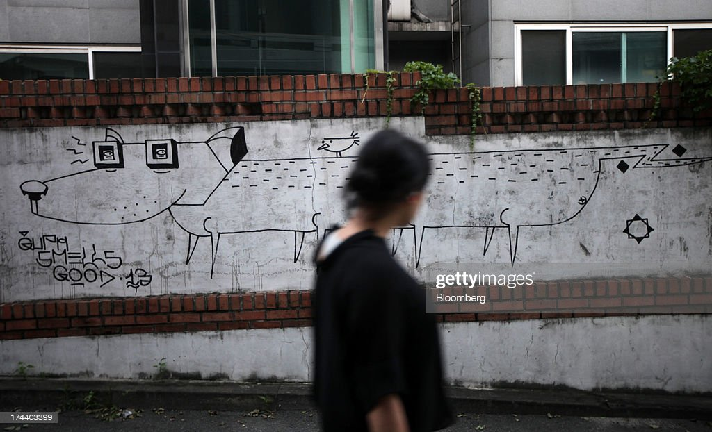 A woman walks past graffiti on a wall in the area of Hannam-dong in Seoul, South Korea, on Wednesday, July 24, 2013. South Koreas economy grew the most in more than two years, on stronger government spending and private consumption even as a slowdown in China clouds the outlook. Photographer: Woohae Cho/Bloomberg via Getty Images