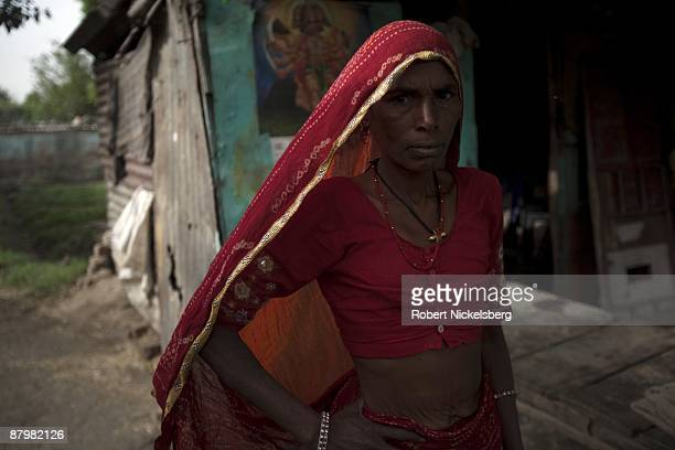 A woman walks past her small brick house in a slum area near a newly dug roadway April 21 2009 where agricultural areas she and members of twelve...