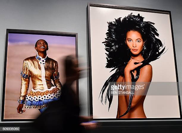 Woman walks past images by Patrick Demarchelier entitled 'Gilt-Laden' of Naomi Campbell 1987 and 'Coque Feathers' of Christy Turlington 1987 as part...