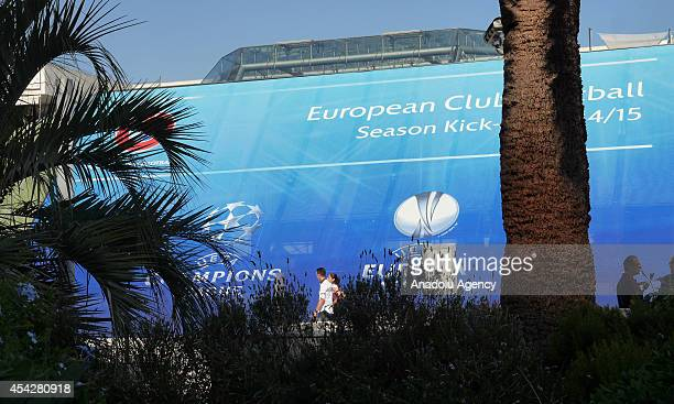 A woman walks past in front of the placard prior to the UEFA Champions League draw in Monaco on August 27 2014 The 32 clubs 22 of which qualified...