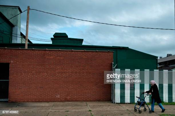 Woman walks past industrial buildings towards Marshall University on April 19, 2017 in Huntington, West Virginia. The city, once an industrial...
