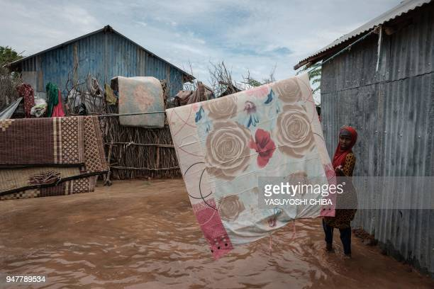 Woman walks past items hung on a line above floodwaters after a heavy rainy season downpour as they seek to fill sandbags at the Dadaab refugee...