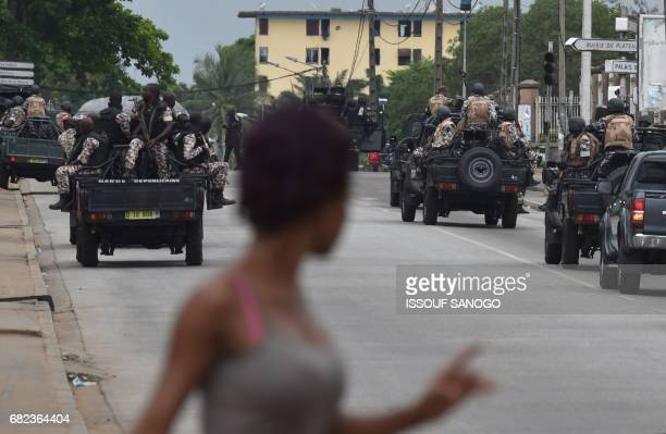 A woman walks past Ivorian soldiers patrolling by Ivory Coast's army headquarters the Gallieni military camp in Abidjan on May 12 2017 after they...