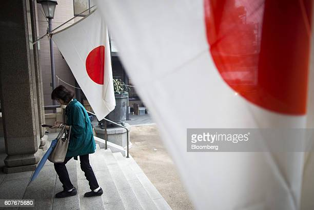 A woman walks past Japanese national flags during an event marking Respect for the Aged Day at a temple in the Sugamo district of Tokyo Japan on...