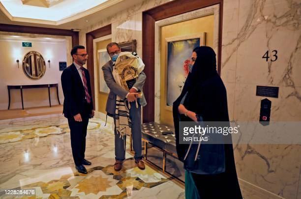 Woman walks past Jewish men, prominent in the Jewish community of Dubai, holding a Torah scroll which they said was brought to Abu Dhabi to mark the...