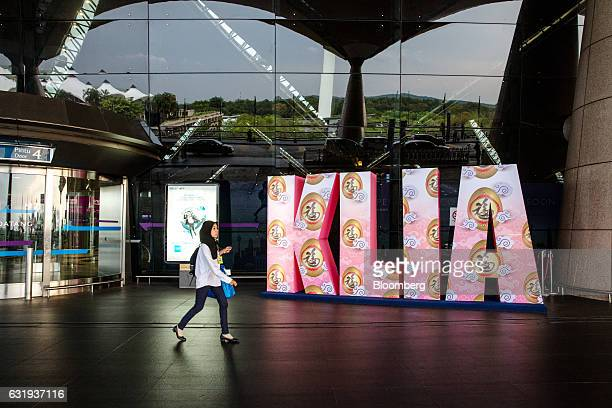 A woman walks past Kuala Lumpur International Airport signage outside the departure hall in Sepang Selangor Malaysia on Tuesday Jan 17 2017 The hunt...