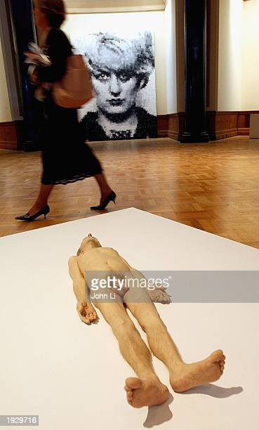 A woman walks past Marcus Harvey's 'Myra' and Ron Mueck's 'Dead Dad' at a press preview of Charles Saatchi's new gallery in the former GLC building...