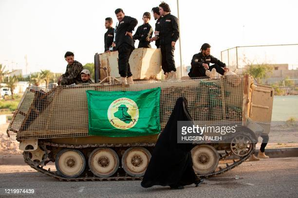 Woman walks past members of the Hashed al-Shaabi paramilitary force taking part in a military parade in the southern Iraqi city of Basra on June 14...