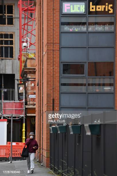 Woman walks past messages pasted inside the windows of the Cambridge Halls student accommodation, for students at Manchester Metropolitan University,...