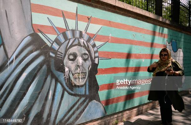 Woman walks past mural painting on the wall of the former US embassy in Tehran, Iran on May 22, 2019.