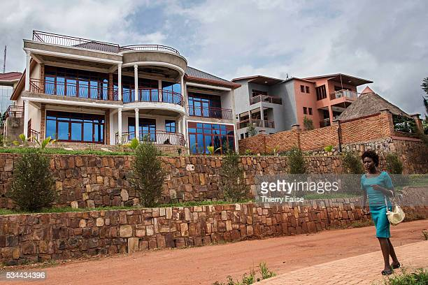 A woman walks past new houses laying on the top of a hill in a affluent district of Kigali Kigali with a population of more than one million is...