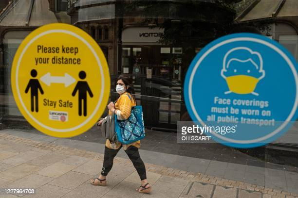 Woman walks past notices on a bus shelter advising people to maintain a social distance and wear face coverings, in the city centre of Preston, north...