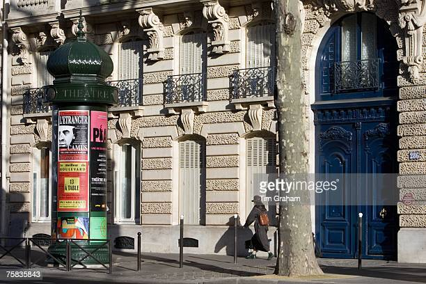 Woman walks past obelisk advertising theatre productions in Parisian street Boulevard St Germain Latin Quarter France