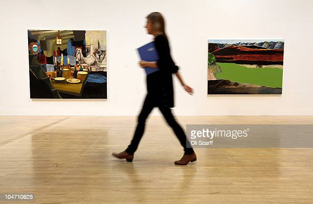 A woman walks past paintings by Dexter Dalwood which have been shortlisted for the Turner Prize 2010 and are displayed in the Tate Britain gallery on...