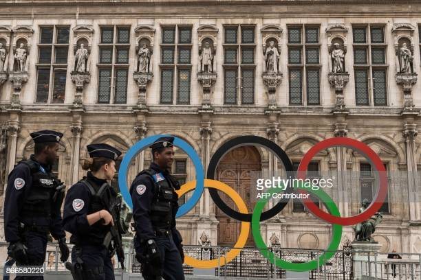 A woman walks past Paris' City Hall where the fiveOlympic rings are on diplay on October 26 after the city was awarded the 2024 Olympics Games / AFP...
