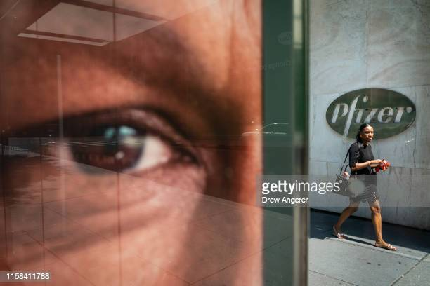 Woman walks past Pfizer world headquarters in Midtown Manhattan on July 29, 2019 in New York City. On Monday morning, Pfizer announced the merger of...