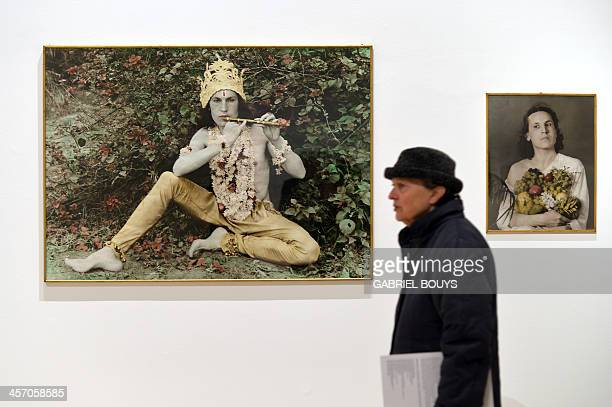 A woman walks past pictures by Luigi Ontani as part of the exhibition Anni 70 Arte a Roma during a press preview at the Palazzo delle Esposizioni on...