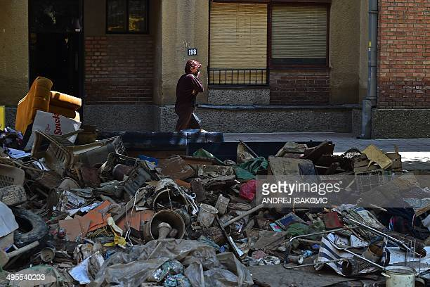 A woman walks past piles of rubbish in Obrenovac 40 kilometres west of Belgrade on June 4 2014 Obrenovac was hit by some of the worst flooding last...