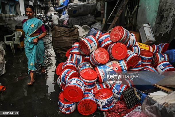 A woman walks past plastic containers for recycling in the Dharavi slum area of Mumbai India on Monday Aug 11 2014 Almost a year after Reserve Bank...