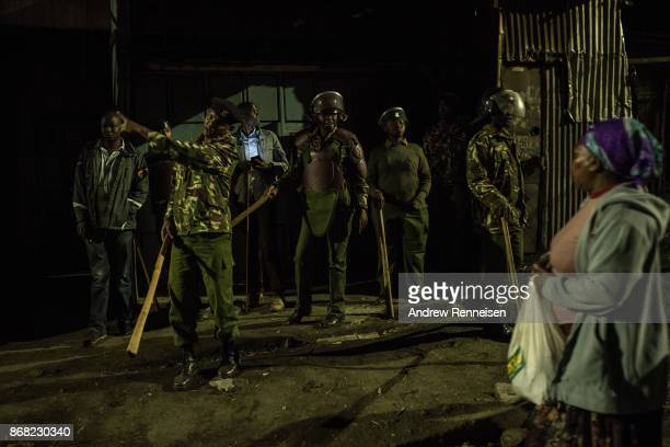 A woman walks past police during unrest after election results were announced in the Mathare slum on October 30 2017 in Nairobi Kenya Uhuru Kenyatta...