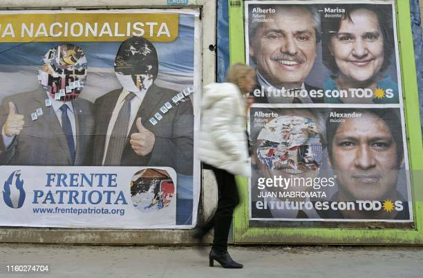 A woman walks past political advertising signs of Frente de Todos party and Frente Patriota party in Buenos Aires on August 7 ahead of Argentina's...