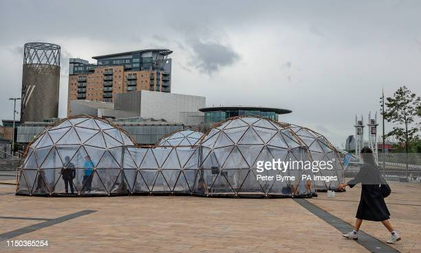 A woman walks past Pollution Pods installed by Cleanairgmcom at MediaCityUK in Manchester People can experience the air quality of cities across the...