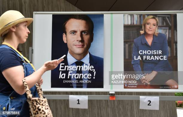 A woman walks past portraits of French presidential candidates former economy minister Emmanuel Macron and farright National Front leader Marine Le...