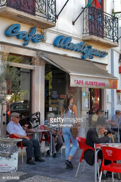 A woman walks past Portuguese men sitting at the Cafe Alentejano on September 29 2016 in Estermoz Portugal The city is located in the Alentejo region...