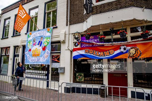 Woman walks past posters and decorations displayed ahead of the visit of the royal family for Koningsdag in Amersfoort, the Netherlands, on April 26,...