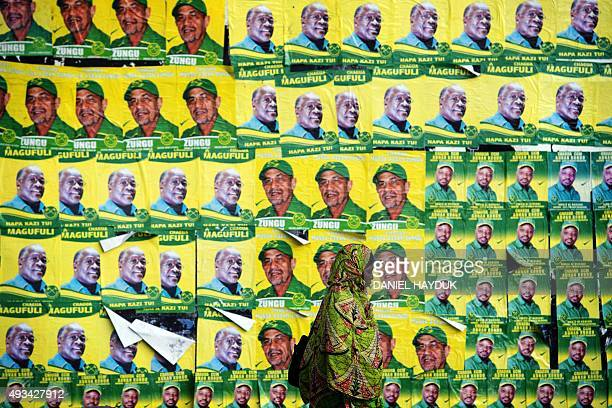 A woman walks past posters for ruling party Chama Cha Mapinduzi presidential candidate John Magufuli and parliamentary candidate Hassan Zungu on...