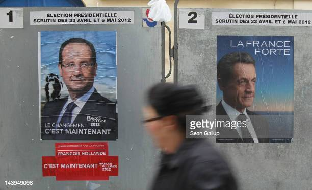 A woman walks past posters outside a polling station that show the two French presidential contenders Francois Hollande and incumbent Nicolas Sarkozy...