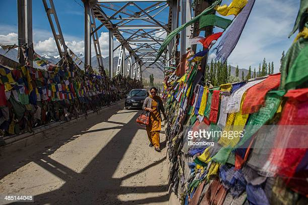 Woman walks past prayer flags on a bridge over the Indus River in Ladakh region, Jammu and Kashmir, India, on Saturday, Aug. 8, 2015. India is...