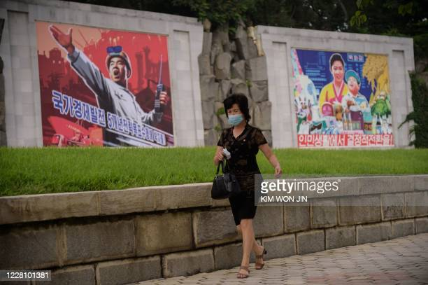 Woman walks past propaganda posters displayed on a street in central Pyongyang on August 19, 2020.
