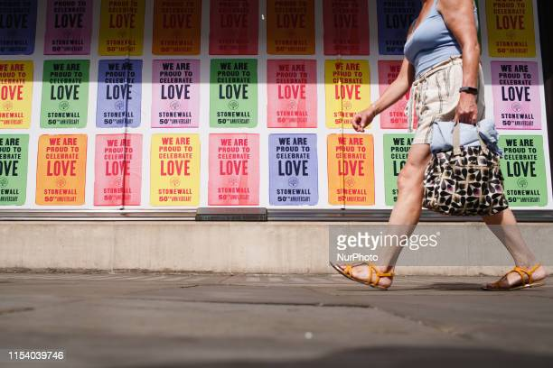 A woman walks past rainbowcoloured posters celebrating New York's 1969 Stonewall uprising on display in the windows of clothing retailer Mulberry on...