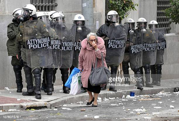 A woman walks past riot police during clashes with protestors December 15 2010 in Athens Greece Violence erupted after approximately 20 000...