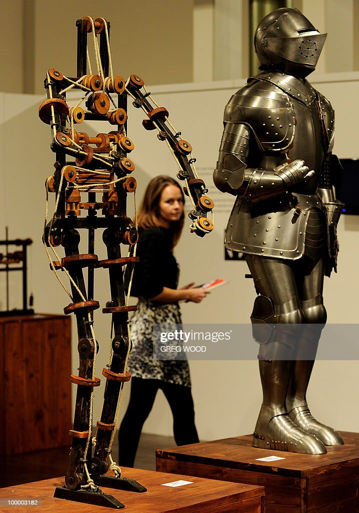 A woman (C) walks past robotic models which form part of the Leonardo da Vinci exhibition Da Vinci Secrets 'Anatomy to Robots' at the Sydney Town Hall on May 20, 2010. The exhibition which runs until August 2, features in excess of 90 exhibits including life like anatomical models and body parts, interactive automatons and robotics all based on his drawings, as well as reproductions of his masterpieces. AFP PHOTO / Greg WOOD