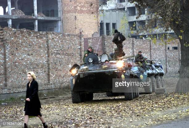 A woman walks past Russian army APCs on a street of Grozny 05 November 2004 Russian forces operating in the breakaway southern republic of Chechnya...
