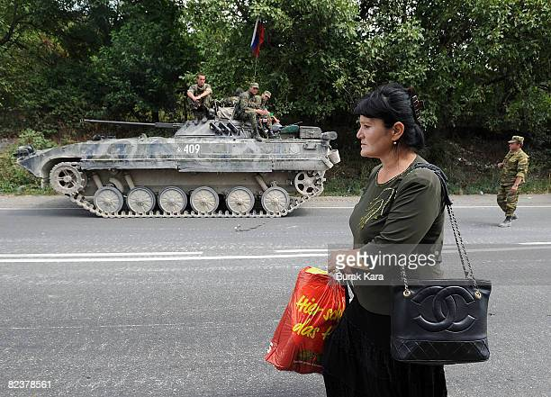 A woman walks past Russian troops on August 16 2008 near the village of Igoeti on the road from Gori to Tbilisi about 45 kilometres from Tbilisi...