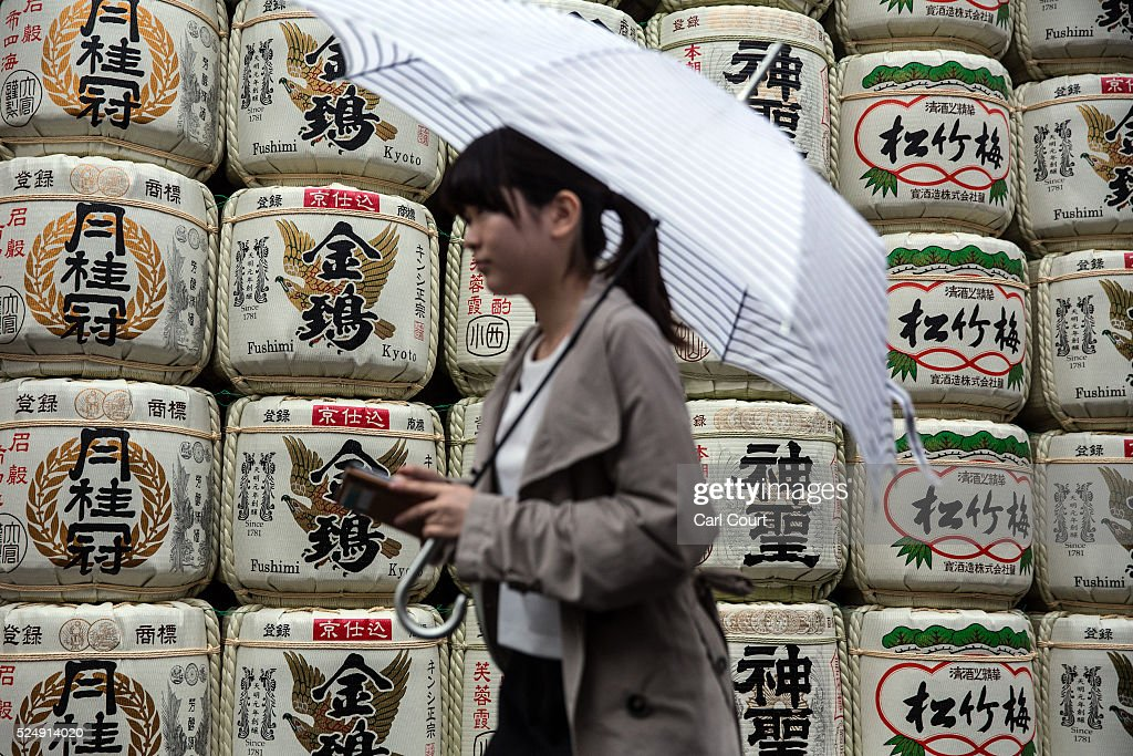 A woman walks past sake barrels on display on April 27, 2016 in Kyoto, Japan. Now the seventh largest city in Japan, Kyoto was once the Imperial capital for more than one thousand years, it is now the capital city of Kyoto Prefecture and a major part of the Kyoto-Osaka-Kobe metropolitan area.