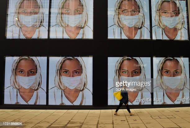 Woman walks past screens displaying a medical worker wearing a face mask at the Flannels store on Oxford Street in London. The screens at the store...